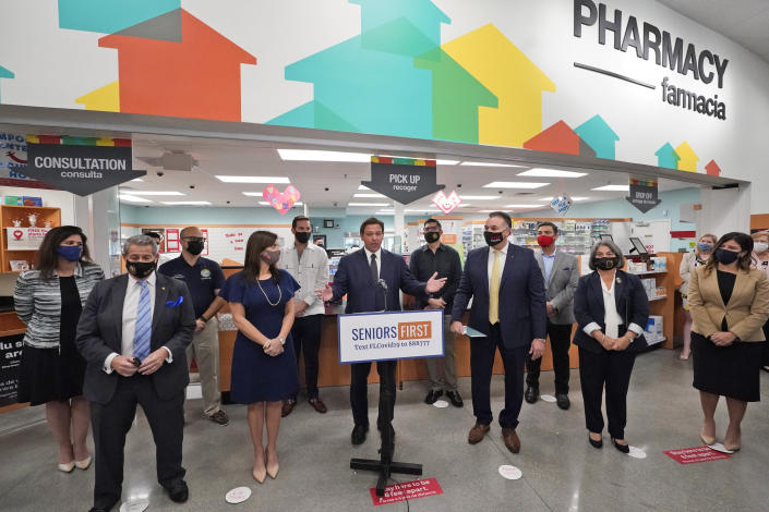 Flanked by other elected officials, Florida Gov. Ron DeSantis, center, gestures as he speaks during a news conference, Tuesday, Feb. 23, 2021, at a Navarro Discount Pharmacy in Hialeah, Fla. DeSantis announced that seniors will soon be able to receive COVID-19 vaccinations at Navarro Discount Pharmacies and CVS y mas pharmacies in Miami-Dade County. (AP Photo/Wilfredo Lee)
