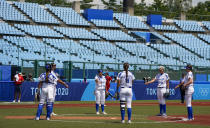 Italian players gather prior to the start of the fifth innings during the softball game between Italy and the United States at the 2020 Summer Olympics, Wednesday, July 21, 2021, in Fukushima , Japan. (AP Photo/Jae C. Hong)