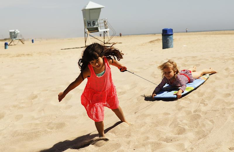 Emily Enholm, 7, and her sister, Hazel, 4, play on the sand at Hueneme Beach. Ventura agreed to allow people to use the city's beaches, pier, promenade and parks as long as they keep their distance from one another and remain on the move.