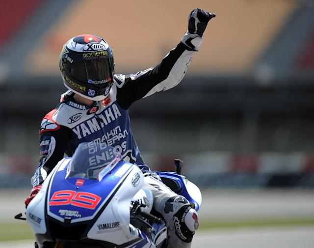 Yamaha Factory Racing's Spanish Jorge Lorenzo waves to supporters at the Catalunya racetrack in Montmelo, near Barcelona, on June 1, 2012, after the MotoGP second training session of the Catalunya Moto GP Grand Prix. AFP PHOTO/LLUIS GENELLUIS GENE/AFP/GettyImages