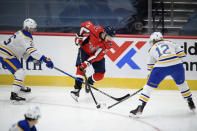 Washington Capitals center Lars Eller (20) skates with the puck between Buffalo Sabres defenseman Rasmus Dahlin (26) and center Eric Staal (12) during the first period of an NHL hockey game, Friday, Jan. 22, 2021, in Washington. (AP Photo/Nick Wass)