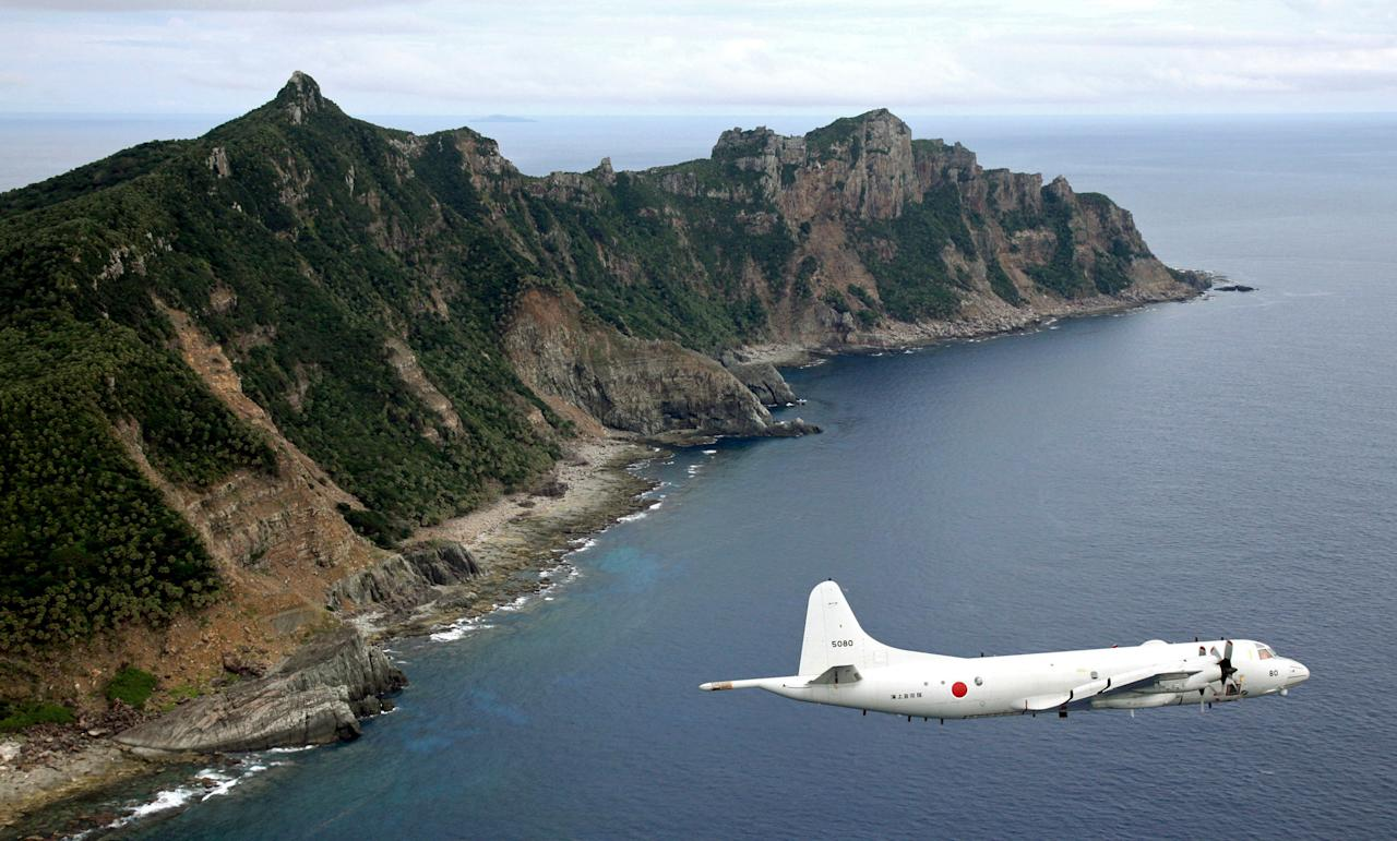 FILE - In this Thursday, Oct. 13, 2011 file photo, Japan Maritime Self-Defense Force's P-3C Orion surveillance plane flies over the disputed islands in the East China Sea, called the Senkaku in Japan and Diaoyu in China. China's new maritime air defense zone is unenforceable and dangerous, Japanese Prime Minister Shinzo Abe said Monday, Nov. 25, 2013 in a continuing war of words over air space that includes the area above islands claimed by both. Abe told a parliamentary session that China's declaration of an air defense identification zone alters the state of affairs in the East China Sea and escalates a tense situation. (AP Photo/Kyodo News, File) JAPAN OUT