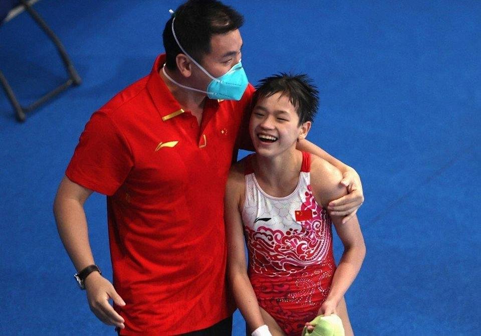 Quan Hongchan celebrates with her coach after a dive at the Tokyo Olympics. Photo: Reuters