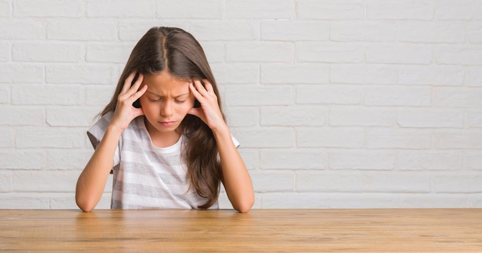 Young hispanic kid sitting on the table at home with hand on head for pain in head because stress. Suffering migraine.