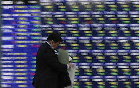 A man walks past a stock quotation board outside a brokerage in Tokyo