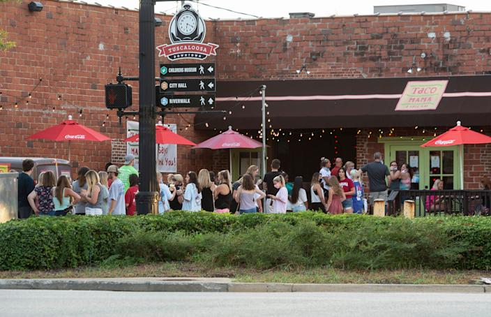 """People line up outside to wait for limited access indoors to order food from Taco Mama in Tuscaloosa, Alabama, on August 15, 2020. <p class=""""copyright"""">AP Photo/Vasha Hunt</p>"""