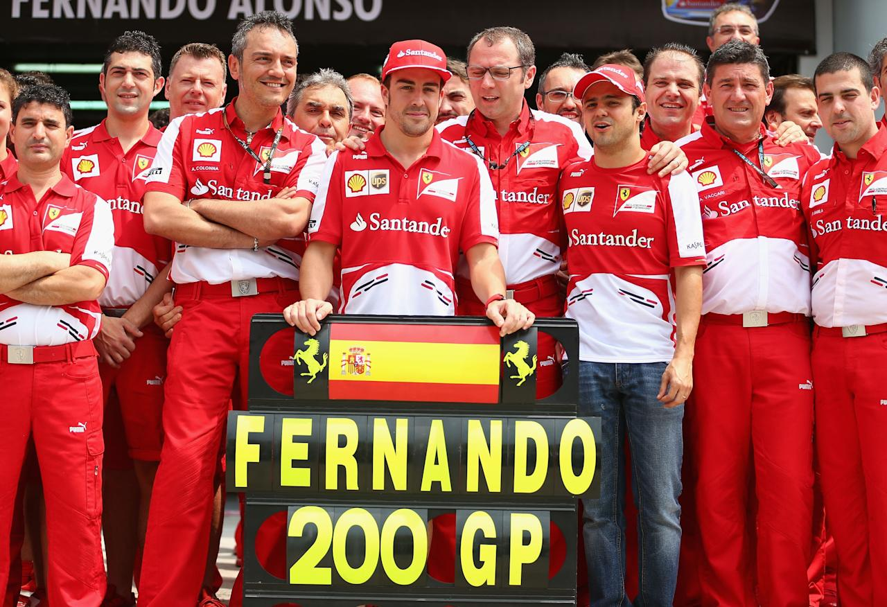 KUALA LUMPUR, MALAYSIA - MARCH 24:  Ferrari team pose for a photograph as their driver Fernando Alonso of Spain celebrates competing in his 200th Grand Prix race during the Malaysian Formula One Grand Prix at the Sepang Circuit on March 24, 2013 in Kuala Lumpur, Malaysia.  (Photo by Clive Mason/Getty Images)