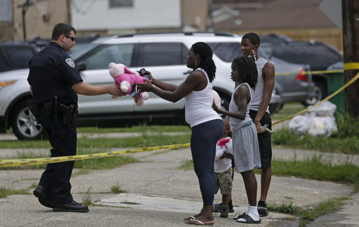 Joanna Jones hands a teddy bear to a Jefferson Parish Sheriff, to place at a makeshift memorial inside a crime scene where the body of missing 6-year-old Ahlittia North was found in Harvey, La., Tuesday, July 16, 2013. Lisa North, the mother of Ahlittia, says Jefferson Parish authorities have found the body of her daughter in a Harvey trash bin. Ahlittia disappeared from her apartment late Friday night or early Saturday morning. North's husband Albert Hill said they were told the body was found in a trash bin not far from their apartment. (AP Photo/Gerald Herbert)