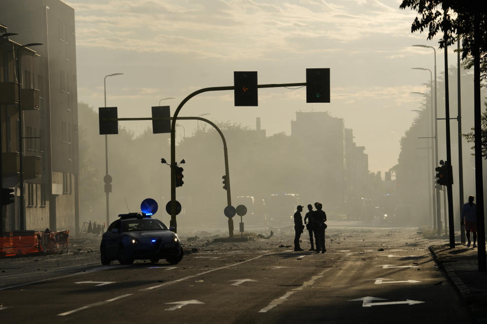 Police patrol the area where a building went on fire in Milan, Italy, Sunday, Aug. 29, 2021. (AP Photo/Luca Bruno)
