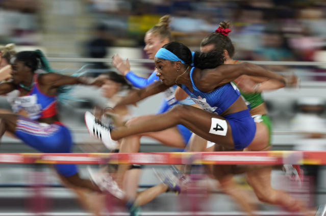 FILE - In this Oct. 5, 2019, file photo, Kendra Harrison, (4) of the United States, competes in a heat of the women's 100 meter hurdles at the World Athletics Championships in Doha, Qatar. The photo was part of a series of images by photographer David J. Phillip which won the Thomas V. diLustro best portfolio award for 2019 given out by the Associated Press Sports Editors during their annual winter meeting in St. Petersburg, Fla. (AP Photo/David J. Phillip, File)