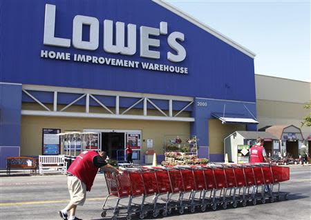 Lowe's workers collect shopping carts in the parking lot at the Lowe's Home Improvement Warehouse in Burbank