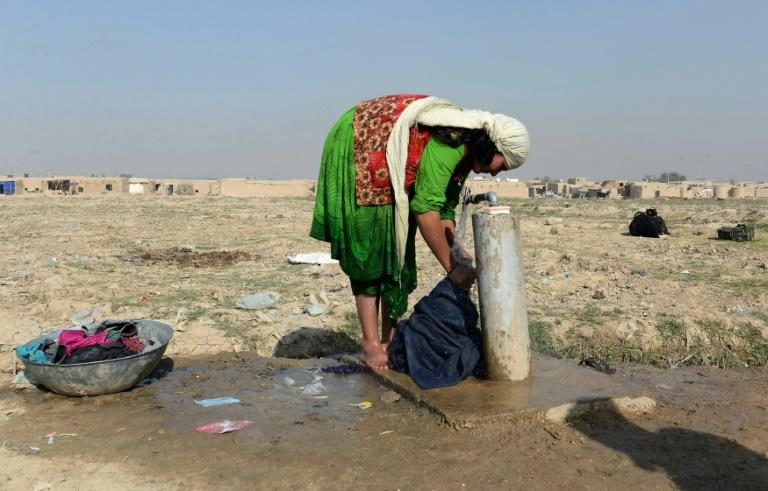 An Afghan Jogi woman washes clothes outside her temporary home on the outskirts of Mazar-i-Sharif