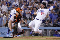 Los Angeles Dodgers' Cody Bellinger, right, scores on a double by Austin Barnes as San Francisco Giants catcher Buster Posey waits for the ball during the sixth inning of a baseball game Tuesday, July 20, 2021, in Los Angeles. (AP Photo/Mark J. Terrill)