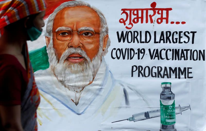 FILE PHOTO: A woman walks past a painting of Indian Prime Minister Narendra Modi a day before the inauguration of the COVID-19 vaccination drive on a street in Mumbai