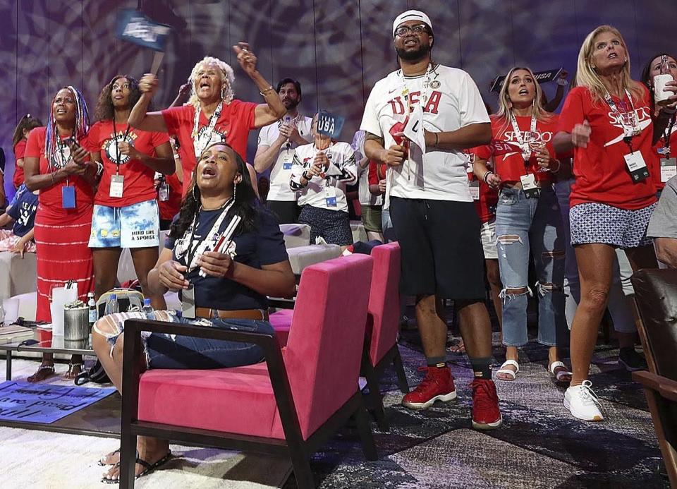 Venus Jewett, back left, mother of Olympic runner Isaiah Jewett, watches her son compete in the 800-meter race and reacts as as Isaiah failed to make the finals as she joins other family and friends of Olympic athletes watching the televised action live at the Olympic Family & Friends Experience at the Loews Sapphire Falls Resort at Universal Orlando in Orlando, Fla., Friday, July 30, 2021. Parents, siblings, friends and former teammates crowd into the ballroom at the resort daily to watch the Summer Games and bond with others in a similar situation, all of them unable to be in Tokyo to root on their loved ones competing for gold because of the coronavirus pandemic. (Stephen M. Dowell/Orlando Sentinel via AP)