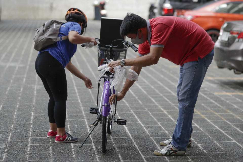 A recipient, left, of a bicycle from the Benjamin Canlas Courage to be Kind Foundation prepares to ride outside a building at the financial district of Manila, Philippines, Saturday, July 11, 2020. Restricted public transportation during the lockdown left many Filipinos walking for hours just to reach their jobs. The foundation saw the need and gave away mountain bikes to nominated individuals who are struggling to hold on to their jobs in a country hard hit by the coronavirus. (AP Photo/Aaron Favila)