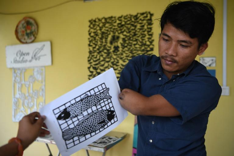 Whispered insults, social isolation, and lost opportunities -- Morn Chear is channeling the stigma he has endured since he lost both his hands a decade ago into artwork that highlights the hardships of Cambodia's disabled (AFP Photo/TANG CHHIN Sothy)