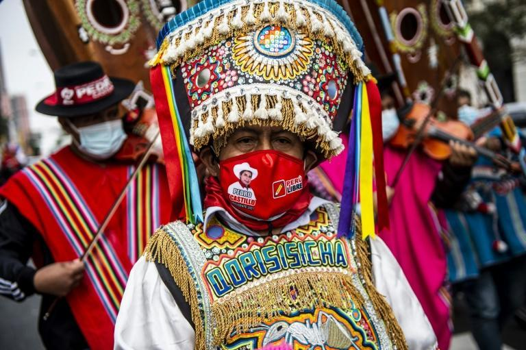 A supporter of leftist Pedro Castillo in colorful regional Andean attire joins the rally in dowtown Lima
