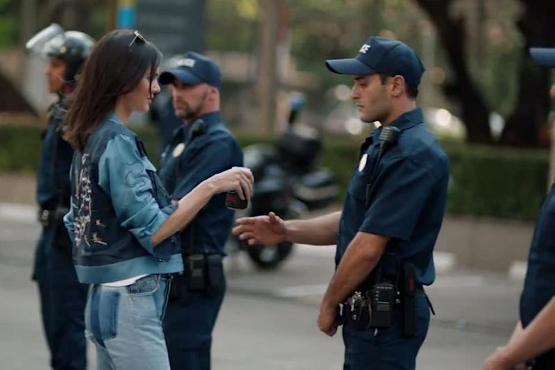 The supermodel hands a police officer a drink of Pepsi in the ad (Pepsi)
