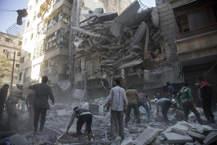 Syrian civilians and rescuers gather at the site of an air strike by government forces in the rebel held neighbourhood of Al-Shaar in Aleppo (AFP Photo/Karam al-Masri)