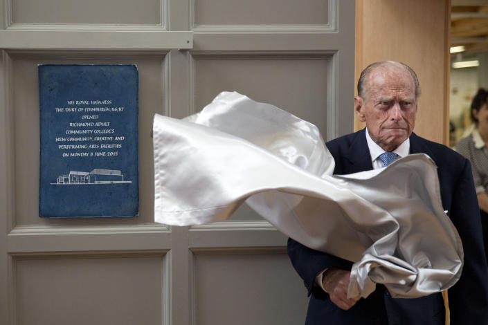 FILE - In this Monday June 8, 2015 file photo, Britain's Prince Philip, the husband of Queen Elizabeth II, unveils a plaque at the end of his visit to Richmond Adult Community College in Richmond, south west London. Buckingham Palace says Prince Philip, husband of Queen Elizabeth II, has died aged 99.(AP Photo/Matt Dunham, Pool, File)
