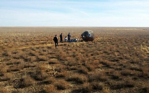 A rescue team arrives at the capsule after it crash landed in the grasslands of Kazakhstan 250 miles from Baikonur cosmodrome - Credit: Russian Central Military District/TASS via Getty Images