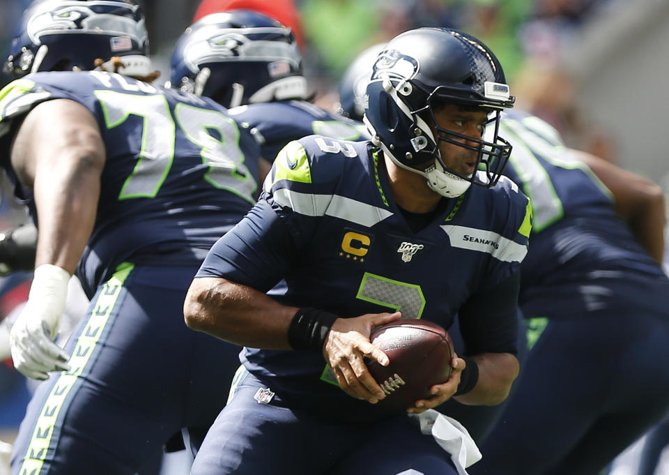 Russell Wilson #3 of the Seattle Seahawks looks to hand off the ball against the Cincinnati Bengals in the first quarter at CenturyLink Field on September 8, 2019 in Seattle, Washington. (Photo by Lindsey Wasson/Getty Images)