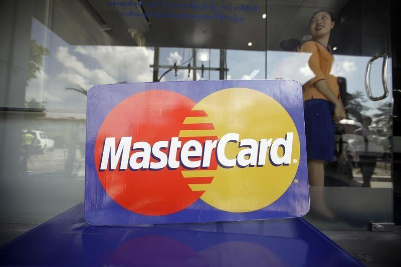 An employee stands behind a MasterCard logo during the launch of the international credit card issuer's first ATM transaction in Myanmar, in Yangon