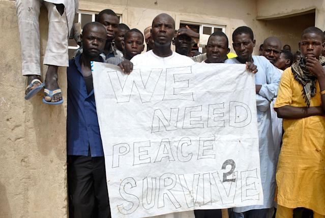 "<p>Nigerian IDPs (Internal Displaced Persons) hold a placard reading ""we need peace to survive"" during the visit of the Nigerian Vice President Yemi Osinbajo to the Bakassi IDPs camp in Maiduguri on June 8, 2017, to launch a major humanitarian aid program. (Photo: Stringer/AFP/Getty Images) </p>"