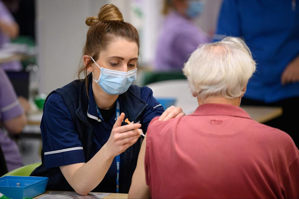 <p>A member of the medical team administers a coronavirus Covid-19 vaccine shot at the NHS vaccination centre in Robertson House in Stevenage</p> (AFP)