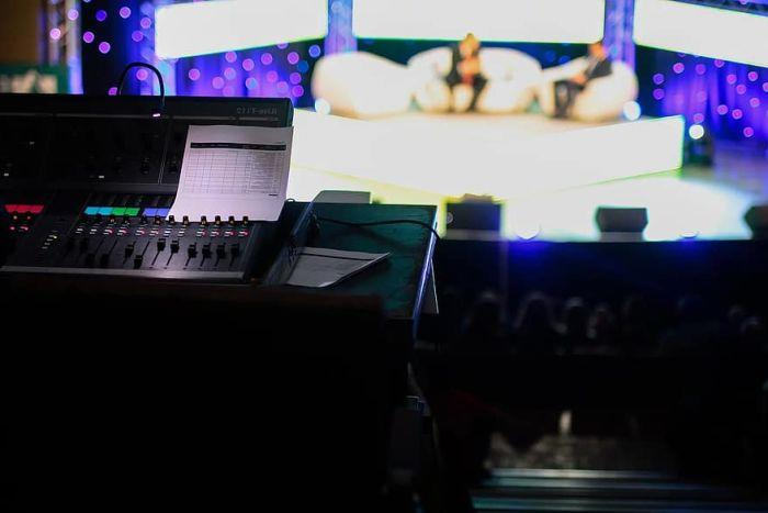 A control board in front of a television studio with two people on a stage.