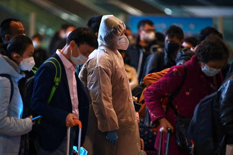 Mask-clad passengers wait in a line after arriving at the railway station in Wuhan, China's central Hubei province on March 28, 2020, after travel restrictions into the city were eased following two months of lockdown due to the COVID-19 coronavirus outbreak. - The Chinese city of 11 million people that was Ground Zero for what became the global coronavirus pandemic partly reopened on March 28 after more than two months of almost total isolation. (Photo by HECTOR RETAMAL / AFP) (Photo by HECTOR RETAMAL/AFP via Getty Images)