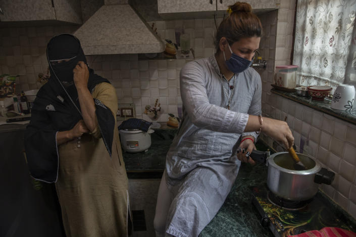 Hinna Bhat, a transgender Kashmiri, cooks as Naina, face covered to hide identity, stands beside during a special meet of their community members in Srinagar, Indian controlled Kashmir, Thursday, June 3, 2021. Life has not been easy for many of Kashmir's transgender people. Most are ostracized by families and bullied in society. They face domestic abuse and end up running away from families at an early age. Some lack housing, education and other basic resources. (AP Photo/ Dar Yasin)
