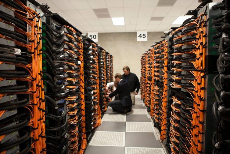 Rows of black boxes linked by orange cables flank a corridor where two people inspect a box
