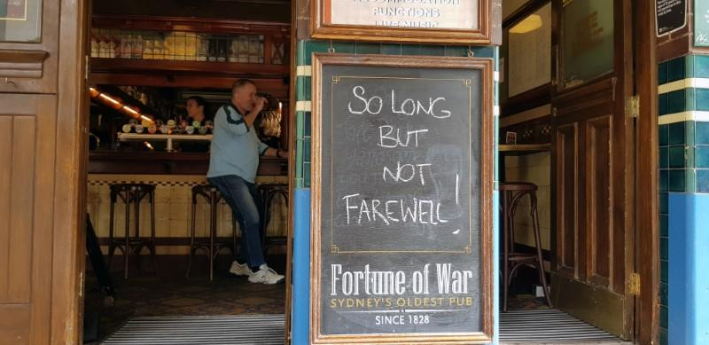Sign in front of Fortune of War pub reads 'so long but not farewell' before it shut down due to coronavirus concerns, in Sydney