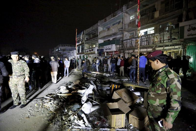 Iraqi security forces gather at the site of car bomb in New Baghdad