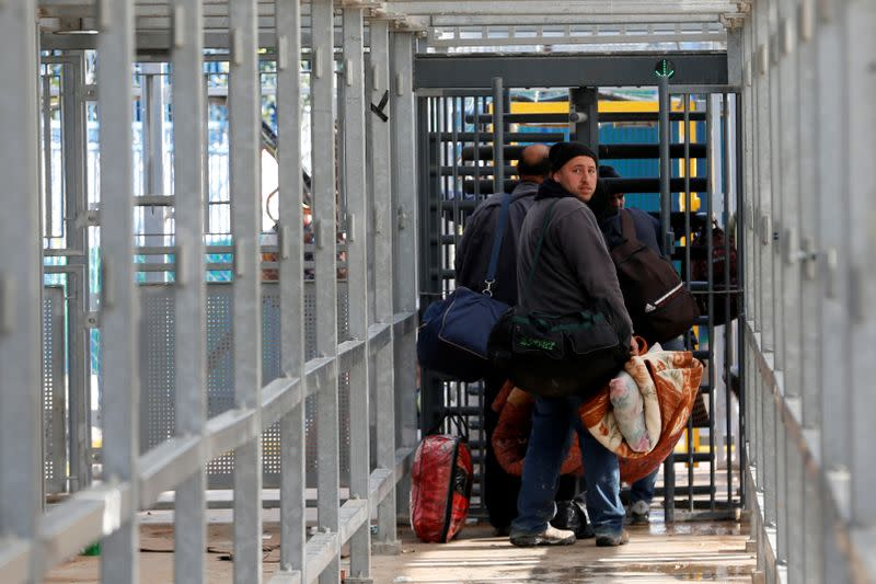Palestinians working in Israel head to work through an Israeli checkpoint, near Hebron in the Israeli-occupied West Bank