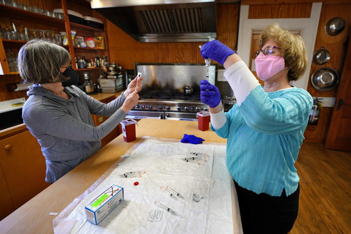 Nurses Sharon Daley, left, and Maureen Giffen fill syringes with the Moderna COVID-19 vaccine in a makeshift clinic in the kitchen of a community center, Friday, March 19, 2021, on Great Cranberry Island, Maine. (AP Photo/Robert F. Bukaty)