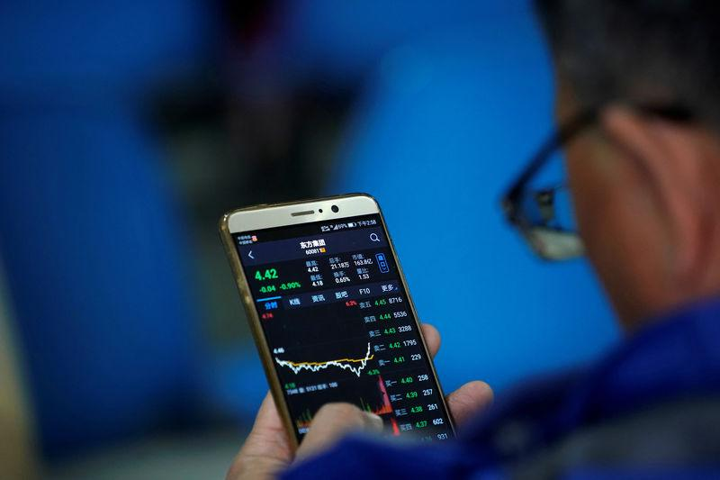 An investor checks stock information on a mobile phone at a brokerage house in Shanghai, China February 9, 2018. REUTERS/Aly Song
