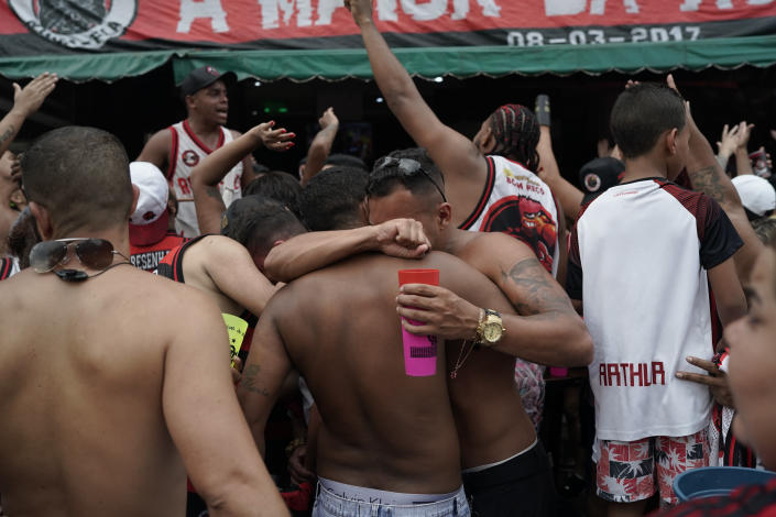 Fans of Brazil's Flamengo soccer team embrace at the end of the FIFA Club World Cup final soccer match against England's Liverpool, at the Rocinha slum in Rio de Janeiro, Brazil, Saturday, Dec. 21, 2019. Liverpool won the match 1-0. (AP Photo/Leo Correa)