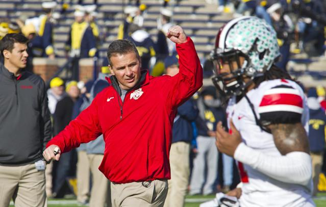 Ohio State head coach Urban Meyer responds to cheers for him from fans in Michigan Stadium as his team takes the field before an NCAA college football game against Michigan in Ann Arbor, Mich., Saturday, Nov. 30, 2013. (AP Photo/Tony Ding)