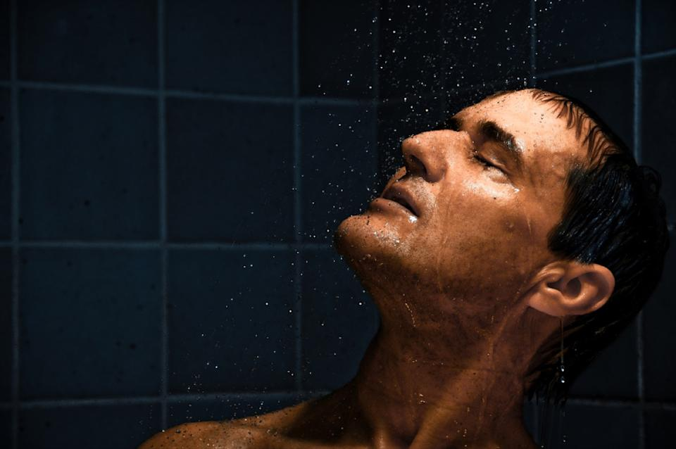 middle aged white man in shower with eyes closed