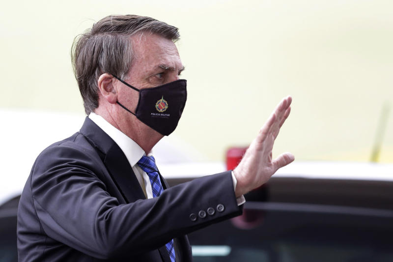 "Brazilian President Jair Bolsonaro wears a mask due to the COVID-19 pandemic as he waves to supporters upon departure from his official residence, Alvorada palace, in Brasilia, Brazil, Monday, May 18, 2020. The logo on the mask reads ""Military Police. Federal District."" (AP Photo/Eraldo Peres)"
