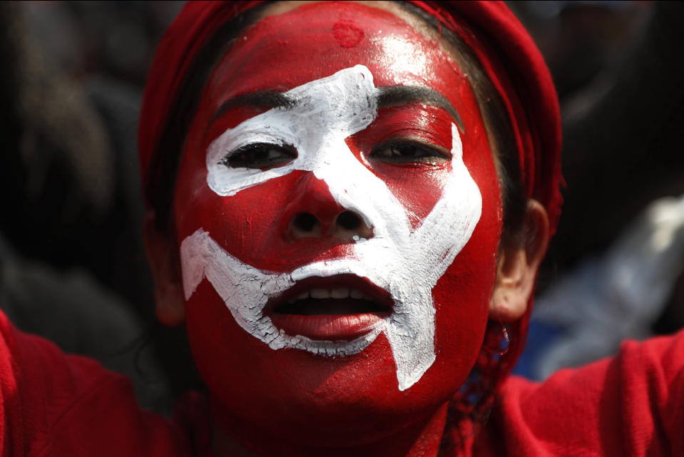 A Nepalese supporter of a splinter group in the governing Nepal Communist Party participates in a rally to celebrate the Supreme Court order in Kathmandu, Nepal, Wednesday, Feb. 24, 2021. Nepal's Supreme Court on Tuesday ordered the reinstatement of Parliament after it was dissolved by the prime minister, in a ruling likely to thrust the Himalayan nation into a political crisis. (AP Photo/Niranjan Shrestha)