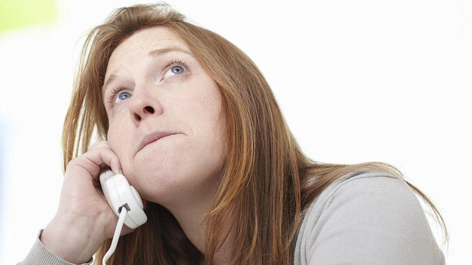 A woman looks to the sky, clearly bored while on hold on the phone pressed to her ear