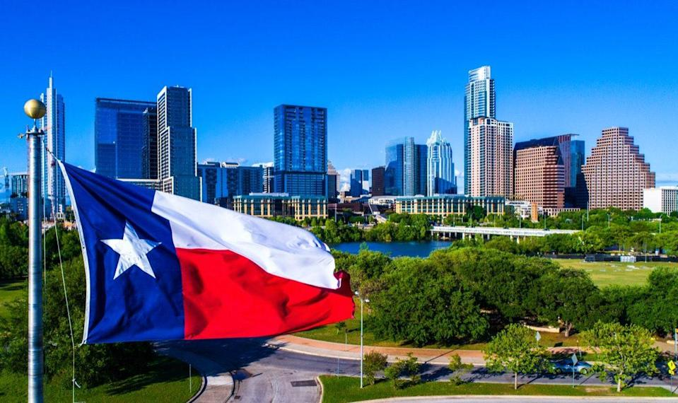 Texas Flag waving in front of the Perfect Austin Texas USA Skyline