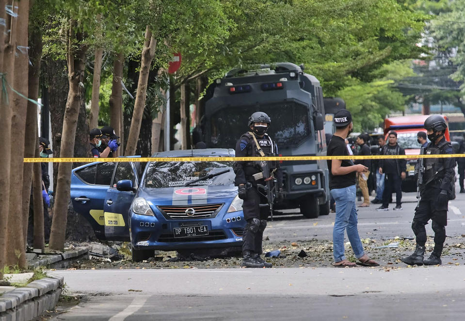 Police officers inspect the area outside the church where an explosion went off in Makassar, South Sulawesi, Indonesia, Sunday, March 28, 2021. A suicide bomber blew himself up outside a packed Roman Catholic cathedral on Indonesia's Sulawesi island during a Palm Sunday Mass, wounding a number of people, police said. (AP Photo/Masyudi S. Firmansyah)