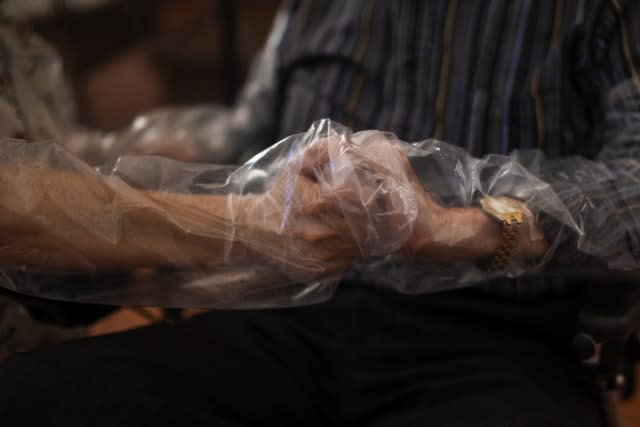 Holding hands through plastic sheeting