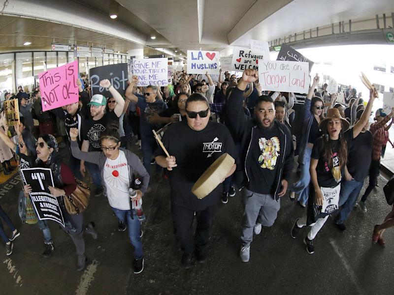 Demonstrators march on the lower roadway as protests against President Donald Trump's executive order banning travel to the U.S: AP