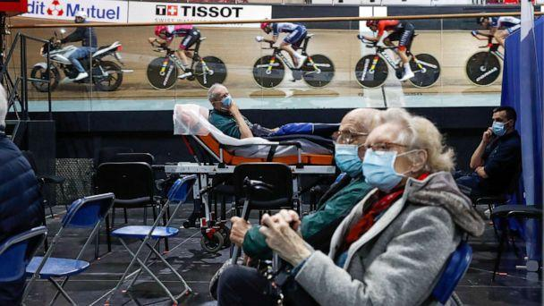 PHOTO: France's national cycling team trains as people wait to get a dose of the 'Comirnaty' Pfizer-BioNTech COVID-19 vaccine at the indoor Velodrome National of Saint-Quentin-en-Yvelines in Montigny-le-Bretonneux, southwest of Paris, March 26, 2021. (Gonzalo Fuentes/Reuters)